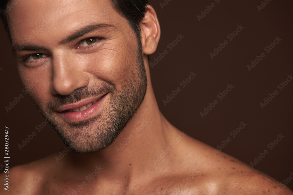 Fototapeta Smiling attractive young man isolated on brown