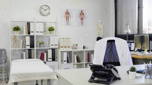 Stampa su Tela  Doctor office table and chair with white lab coat on it and white paper nobody