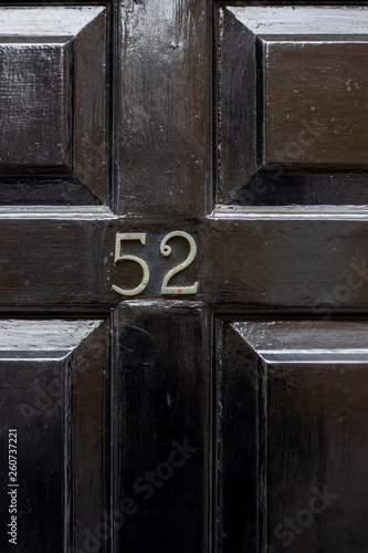 Fotografia  House number 52 with the fifty two on a shiny black wooden door in the centre of
