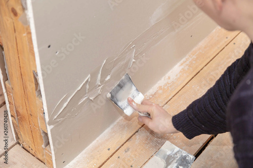 Photo Worker aligns the walls with plaster. Repair in the house