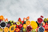 Healthy raw rainbow fruits background, mango papaya strawberries oranges passion fruits berries on oval serving plate on light kitchen top, top view, copy space, selective focus