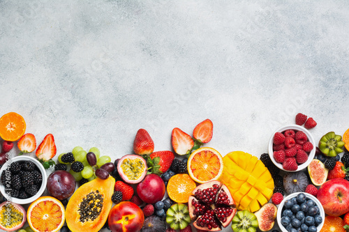 Healthy raw rainbow fruits background, mango papaya strawberries oranges passion fruits berries on oval serving plate on light kitchen top, top view, copy space, selective focus - 260742648