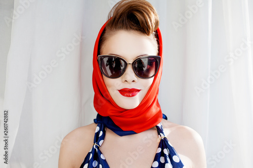 Fotografia  young beautiful woman with red lipstick and a headscarf.