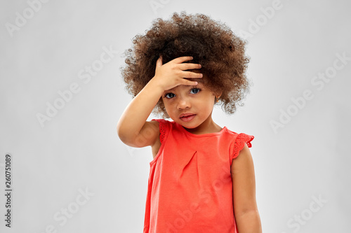 Obraz childhood and people concept - sad little african american girl touching her forehead over grey background - fototapety do salonu