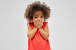 childhood, expression and emotion concept - confused little african american girl covering mouth by hands over grey background