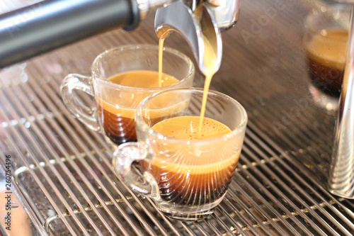 Fotomural  Black coffee being brewed by the machine