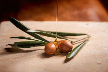 Argan oil puring over argan seeds