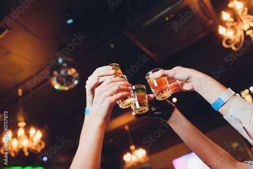 Cuadros en Lienzo  Hand holding a glass shot with vodka shot.