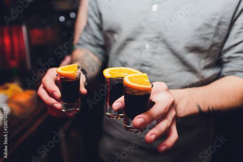 Fotografie, Obraz  Jagermeister Shots cocktails with orange hand male.