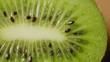 Overhead Extreme Closeup Shot Of Rotating Kiwi Slice On Table