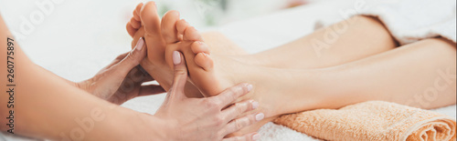 Fototapeta panoramic shot of masseur doing foot massage to adult woman in spa