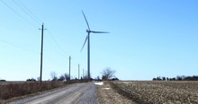 A Wind Turbine Along A Country Road 4K