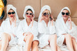 Leisure time at spa. Women relaxation time. Row of BFF in sunglasses and bathrobes talking on smartphones. Bare legs.