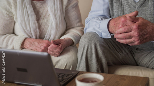 Photographie  Headless grandparents hands in focus with a laptop in front