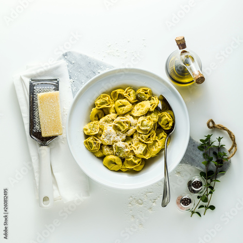plate of italian cooked ravioli tortellini with parmesan cheese on the table Wallpaper Mural