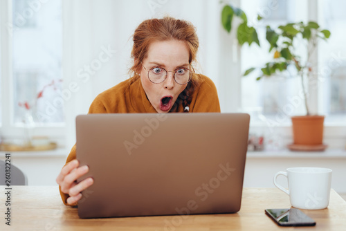 Horrified young woman staring aghast at a laptop Wallpaper Mural
