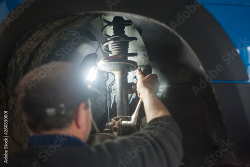 mechanic man working on the car shock absorber Wallpaper Mural
