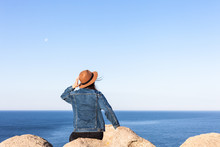 Closeup Back View Of Woman In Jeans Jacket And Hat Sitting And Looking At Blue Ocean And Sky.