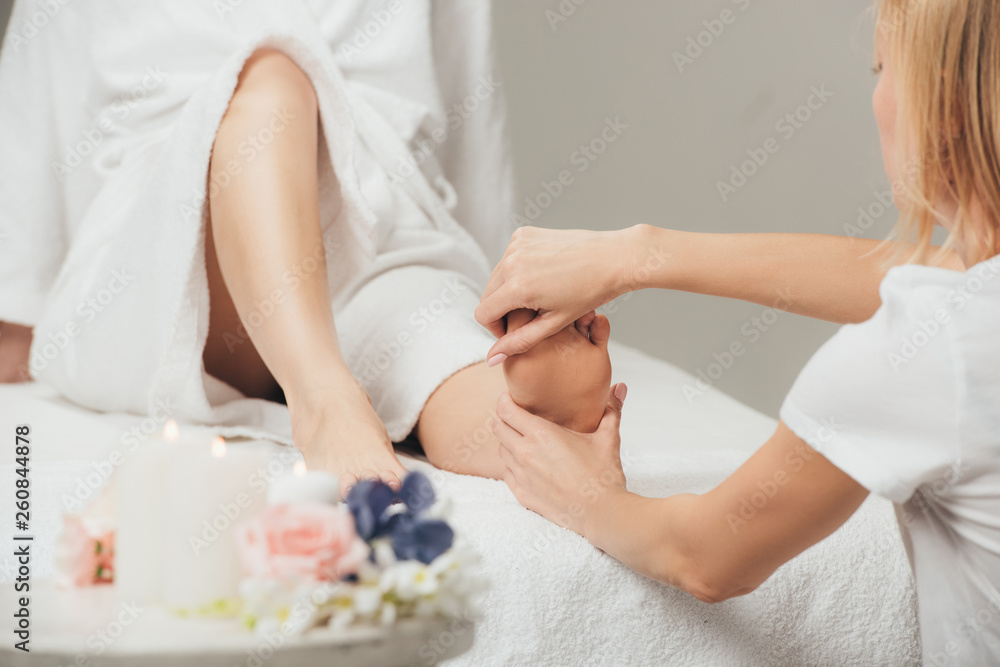 Fototapeta cropped view of masseur doing foot massage to adult woman in spa