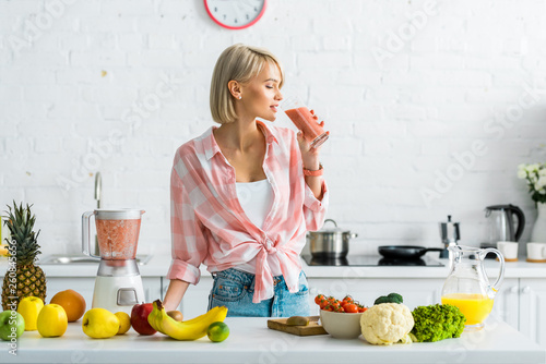 attractive blonde woman drinking tasty smoothie near ingredients in kitchen Wallpaper Mural