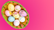 Wicker Basket With Easter Eggs Hand Painted On Color Tabletop Background