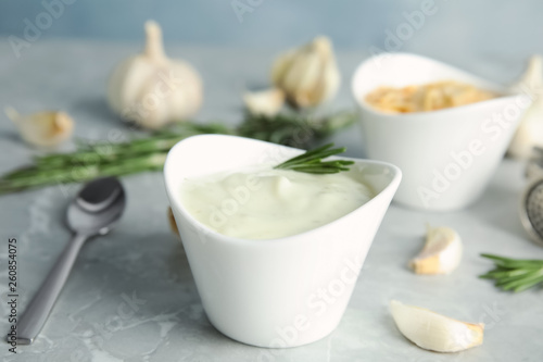 Composition with bowl of garlic sauce on grey table Canvas Print