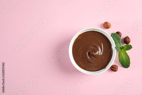 Photo  Dessert bowl with sweet chocolate cream, hazelnuts and mint on color background, top view