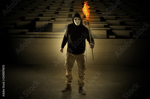 Ugly, aberrant man coming out from the labyrinth with burning flambeau on his ha Wallpaper Mural