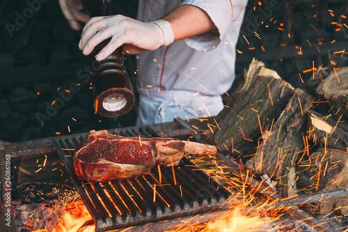Fotografia Chef pepper the steak on fire.