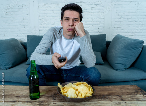 Bored young man sitting on the couch watching TV switching channels looking for Canvas Print