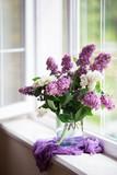 Spring tender bouquet of beautiful lilac in glass vase near window in daylight