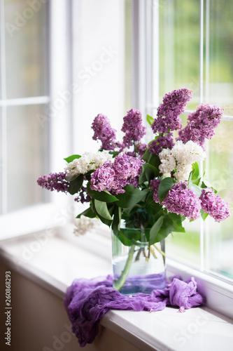 Fototapeta Spring tender bouquet of beautiful lilac in glass vase near window in daylight