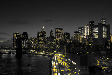 Panel Szklany Współczesny New York City black and white night skyline with golden yellow lights glowing in downtown Manhattan