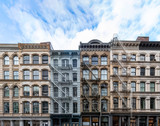 Fototapeta Nowy York - Exterior view of old apartment buildings in the SoHo neighborhood of Manhattan in New York City with empty blue sky