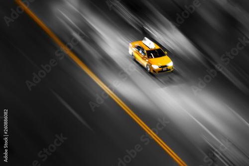 New York City yellow taxi in motion speeding down the street on a blurred background