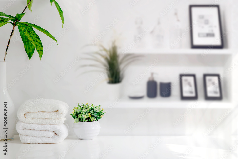Fototapeta Mockup bath towels on wooden table in white room with copy space.