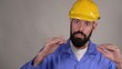 Portrait of young worker in yellow helmet explain something and show ok gesture on gray background