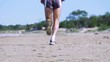 Running sportsman on summer beach is moving away. Closeup low angle shot