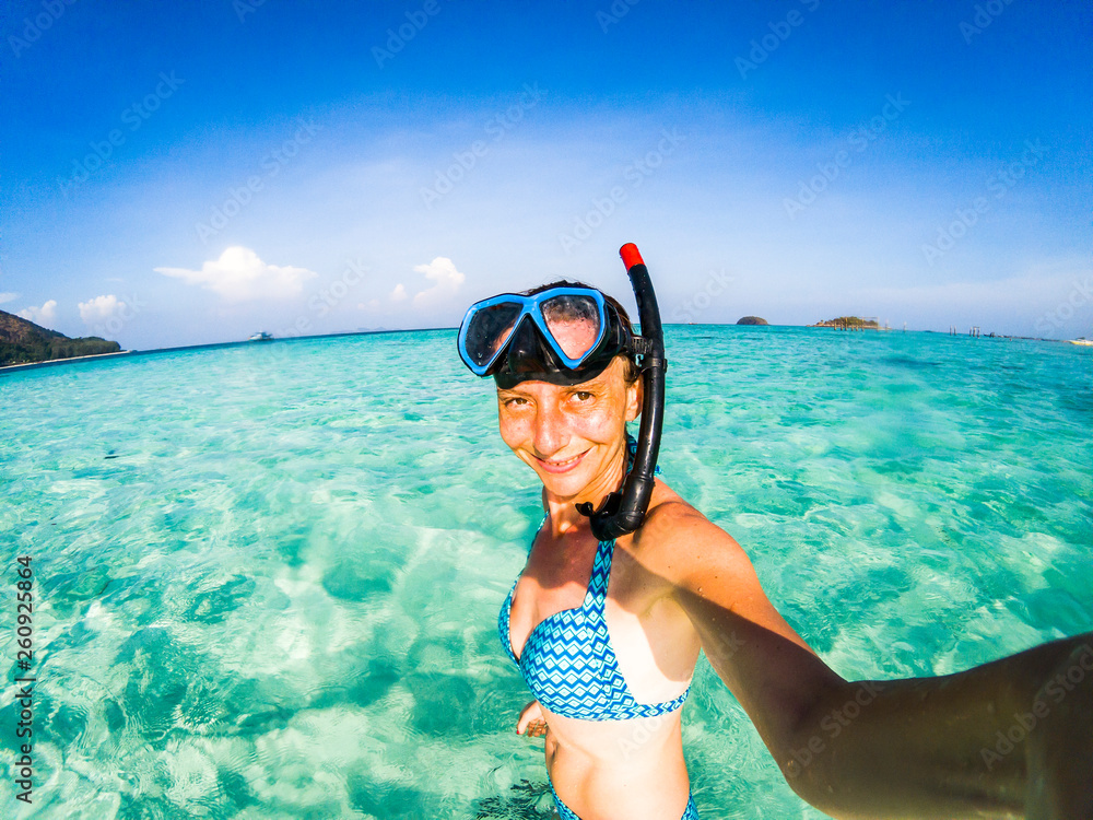 Fototapety, obrazy: woman taking an underwater selfie while snorkeling in crystal clear tropical water