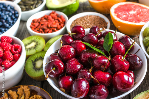 Bowl with red cherries and other healthy food for breakfast containing organic superfood like fresh fruits and seeds Wallpaper Mural