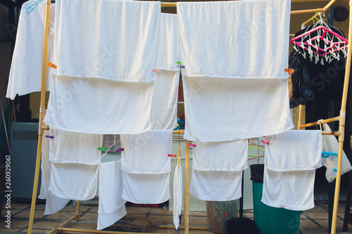 Fototapety, obrazy: Drying clothes in the unusual sunset. White towels and sheets dry in the sun on stretched laundry ropes. Washing laundry from the laundry is dried in the sun on dryers with clothespins.