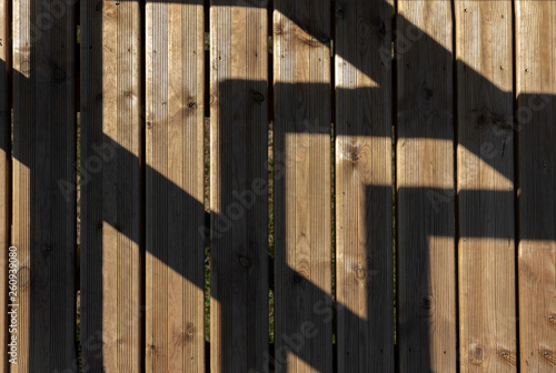 Fotografiet  Sunlit shadows on wooden bridge