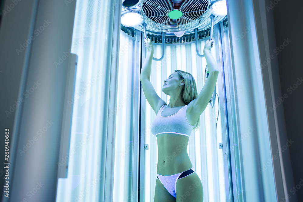 Fototapety, obrazy: Close-up of a cute elegant girl enjoying a tan in a modern solarium. Portrait of a healthy young woman in a solarium, she holds her hands up and closes her eyes with pleasure