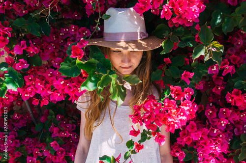 Portrait of girl among purple bougainvillaea Wallpaper Mural