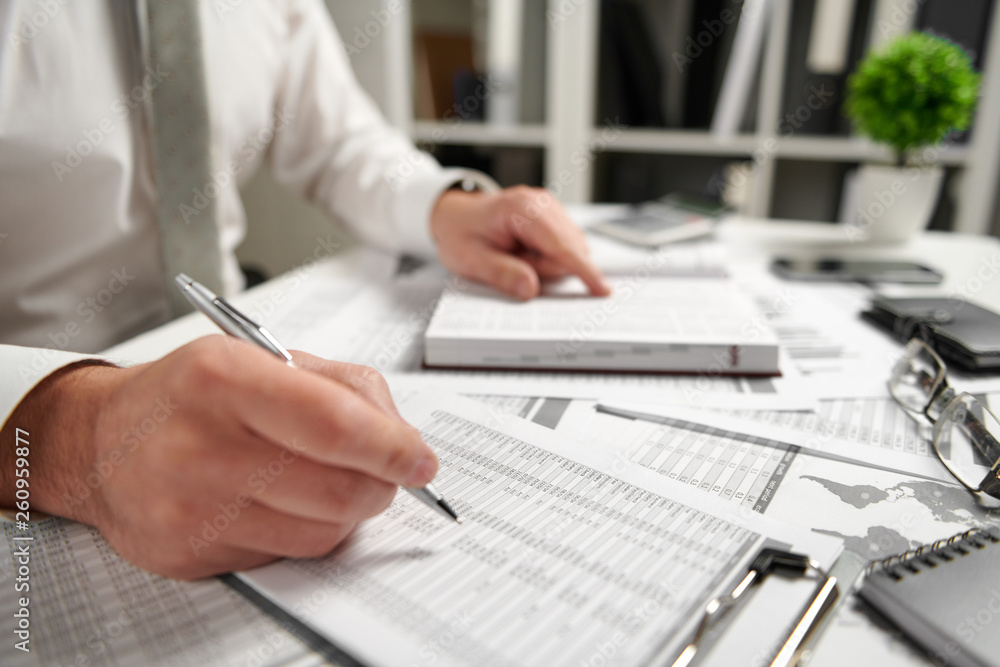 Fototapeta Businessman working at office and calculating finance, reads and writes reports. Business financial accounting concept.