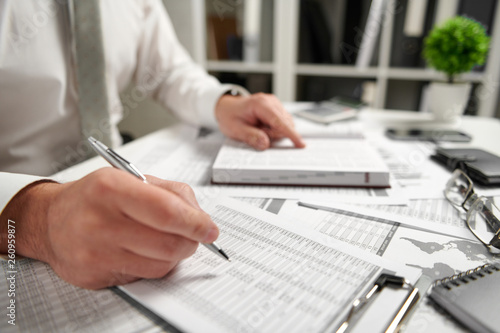 Fototapeta Businessman working at office and calculating finance, reads and writes reports. Business financial accounting concept. obraz