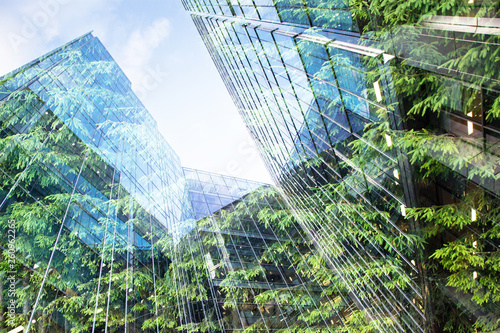 Fotografering green city - double exposure of lush green forest and modern skyscrapers windows