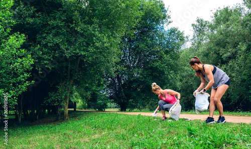 Photographie  Two girls running with bags doing plogging outdoors