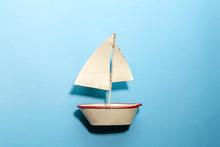 青背景の上に白いブリキのヨットを置いて海のイメージ