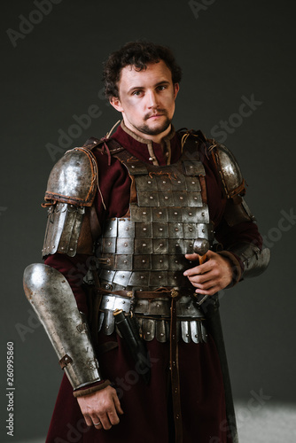 Fotografía Medieval man knight in armor and weapon on dark background